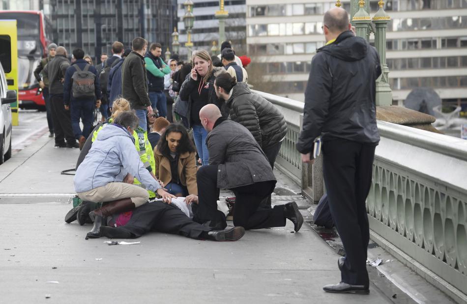Kolemjdoucí ošetřují zraněné na Westminster Bridge