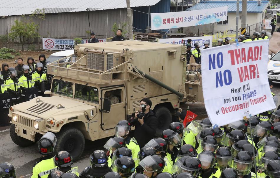 Americké vojenské auto projíždí kolem transparentů proti systému THAAD