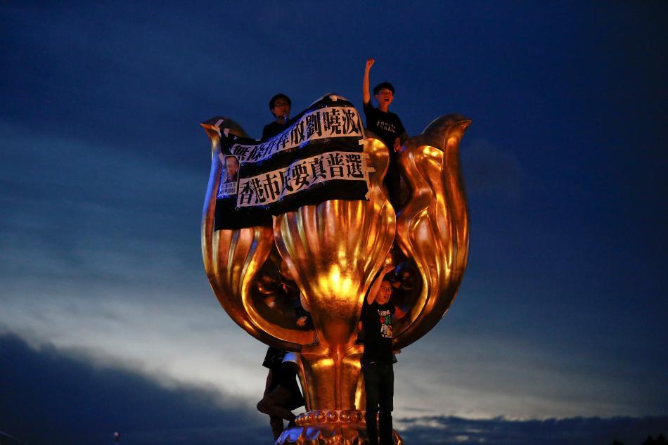Kritické nápisy na zlaté soše upomínající k výročí