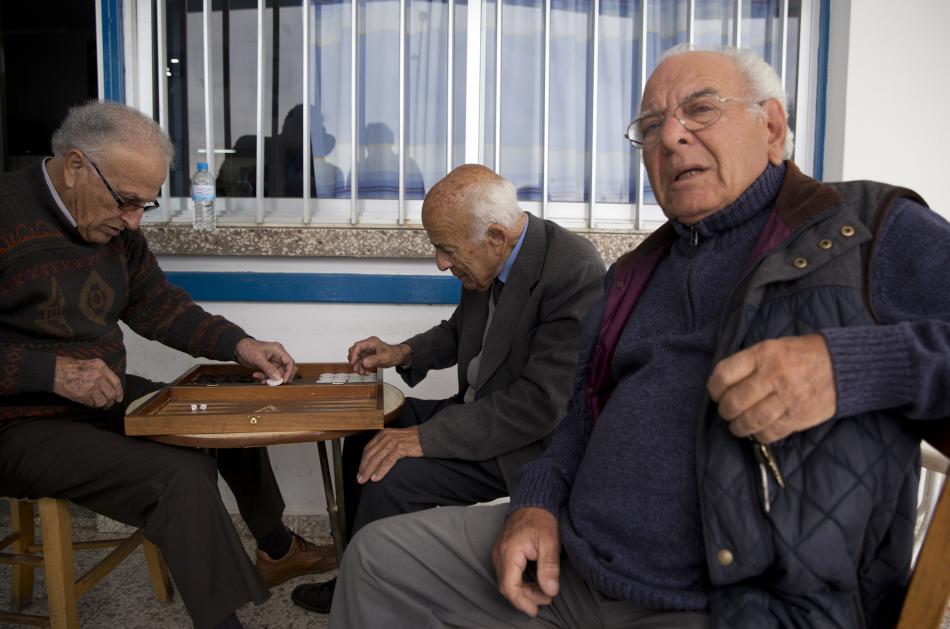 Muži na terase kavárny v Pyle hrají vrhcáby