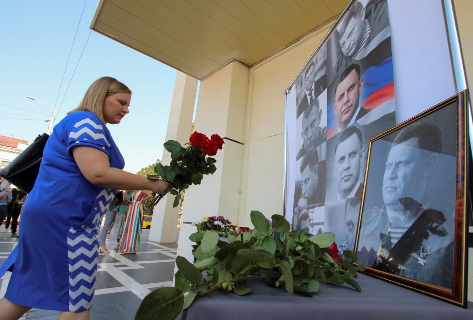 Obyvatelka Krymu nese květinu k fotkám zavražděného lídra doněckých povstalců Alexandra Zacharčenka