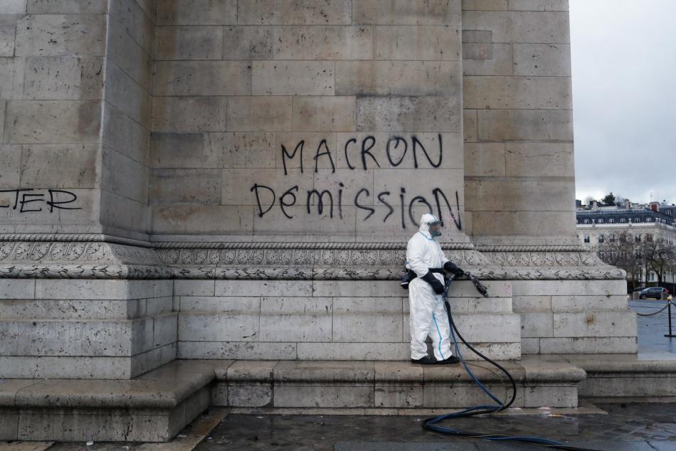 Muž se chystá očistit nápis, který požaduje demisi prezidenta Macrona.