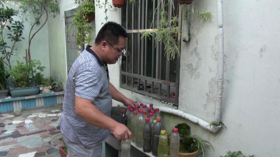 Ekologický aktivista Wu Li-chung sbírá vzorky vody z jezera Tchaj